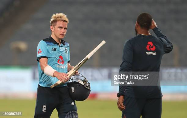 Sam Curran of England interacts with team mate Chris Jordan following the 3rd One Day International match between India and England at MCA Stadium on...