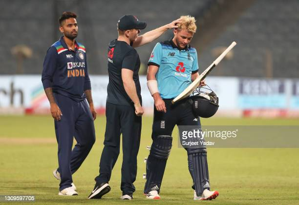 Sam Curran of England interacts with team mate Eoin Morgan following the 3rd One Day International match between India and England at MCA Stadium on...