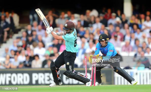 Sam Curran of Surrey is bowled by Will Beer of Sussex Sharks as Alex Carey of Sussex Sharks looks on during the Vitality T20 Blast match between...