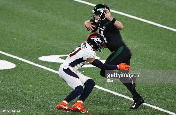 Sam Darnold of the New York Jets breaks a tackle and runs for a touchdown against Justin Simmons of the Denver Broncos during the first quarter at...