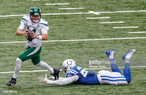 Sam Darnold of the New York Jets escapes the tackle from DeForest Buckner of the Indianapolis Colts during the first half at Lucas Oil Stadium on...