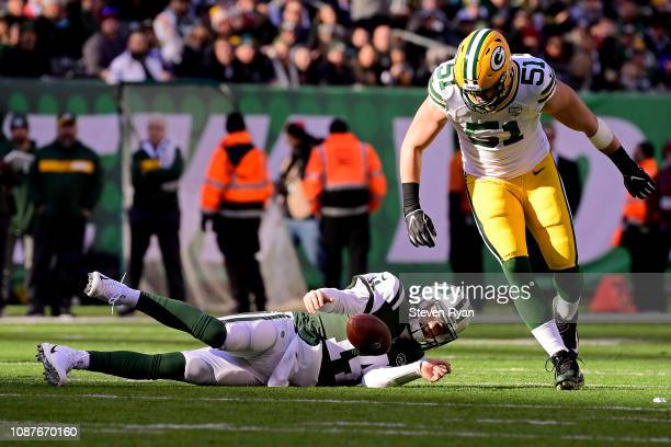 Sam Darnold of the New York Jets gets tripped up under pressure from Kyler Fackrell of the Green Bay Packers at MetLife Stadium on December 23 2018...