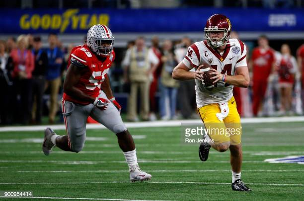 Sam Darnold of the USC Trojans runs from Tyquan Lewis of the Ohio State Buckeyes in the second half of the 82nd Goodyear Cotton Bowl Classic between...