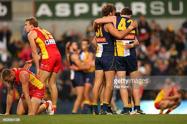 Sam Day and Tom Lynch of the Suns react as Will Schofield Jeremy McGovern and Sharrod Wellingham of the Eagles celebrate winning the round 13 AFL...