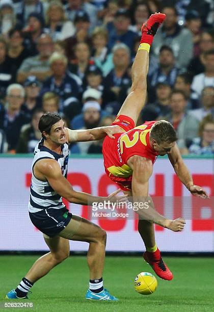 Sam Day of the Suns crashes to the ground after a contest with Shane Kersten of the Cats during the round six AFL match between the Geelong Cats and...