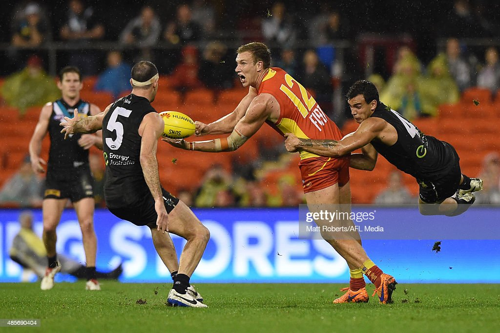 Sam Day of the Suns handballs under pressure during the round 22 AFL match between the Gold Coast Suns and the Port Adelaide Power at Metricon Stadium on August 29, 2015 on the Gold Coast, Australia.