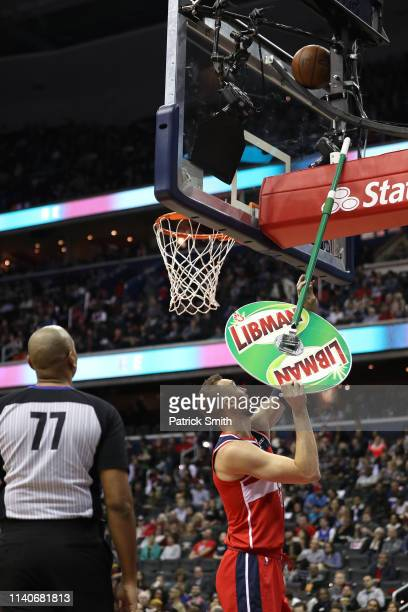 Sam Dekker of the Washington Wizards uses a floor mop to dislodge the basketball from the backboard against the San Antonio Spurs during the first...