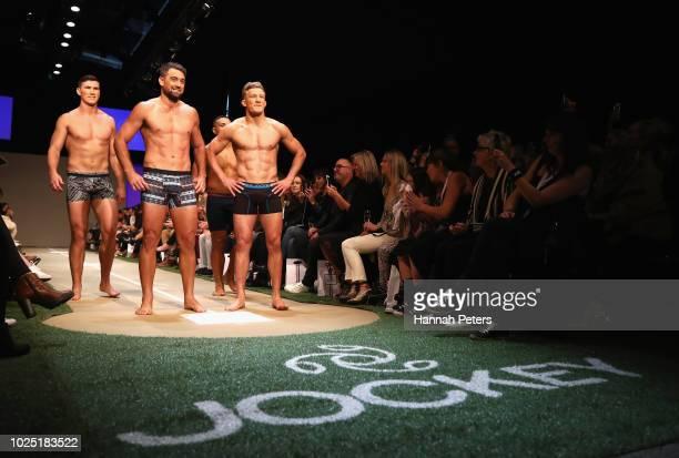 Sam Dickson of the New Zealand rugby sevens team, Kurt Baker and Damian McKenzie of the New Zealand All Blacks walk the runway during the Jockey show...