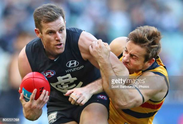Sam Docherty of the Blues is tackled by Richard Douglas of the Crows during the round 15 AFL match between the Carlton Blues and the Adelaide Crows...