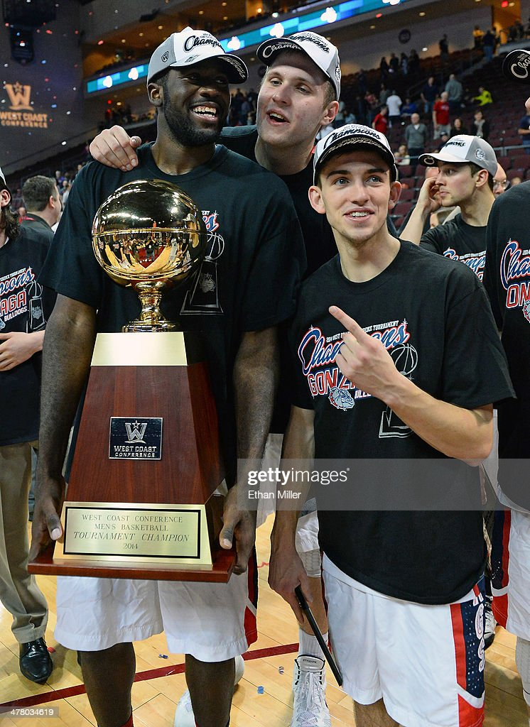 Sam Dower #35, Przemek Karnowski #24 and David Stockton #11 of the Gonzaga Bulldogs pose on the court with the trophy after winning the championship game of the West Coast Conference Basketball tournament 75-64 over the Brigham Young Cougars at the Orleans Arena on March 11, 2014 in Las Vegas, Nevada.