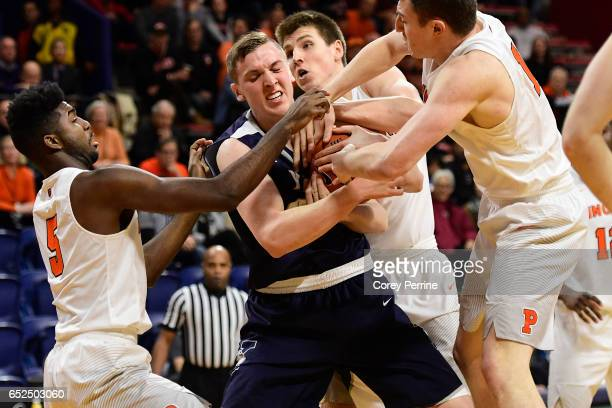 Sam Downey of the Yale Bulldogs fights for the ball from Amir Bell Spencer Weisz and Will Gladson of the Princeton Tigers during the first half of...