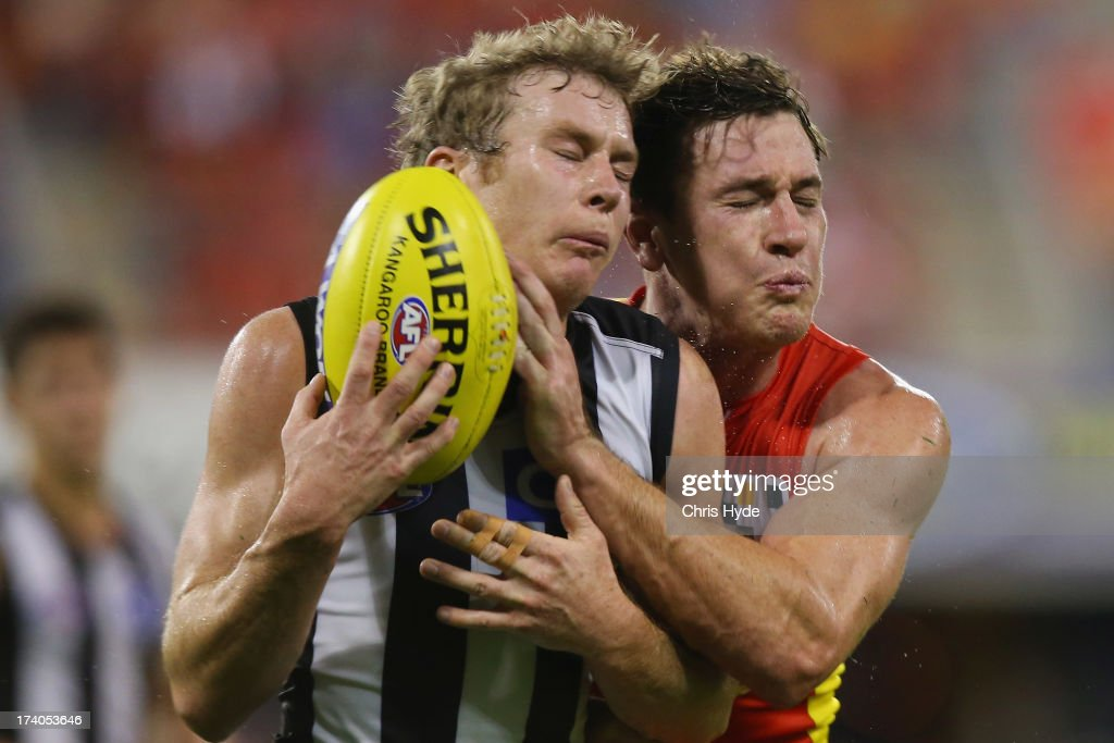 Sam Dwyer of the Magpies is tackled by Danny Stanley of the Suns during the round 17 AFL match between the Gold Coast Suns and the Collingwood Magpies at Metricon Stadium on July 20, 2013 in Gold Coast, Australia.
