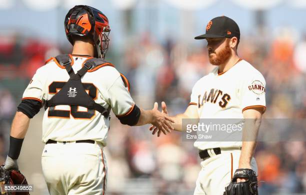Sam Dyson shakes hands with Buster Posey of the San Francisco Giants after they beat the Milwaukee Brewers at ATT Park on August 23 2017 in San...