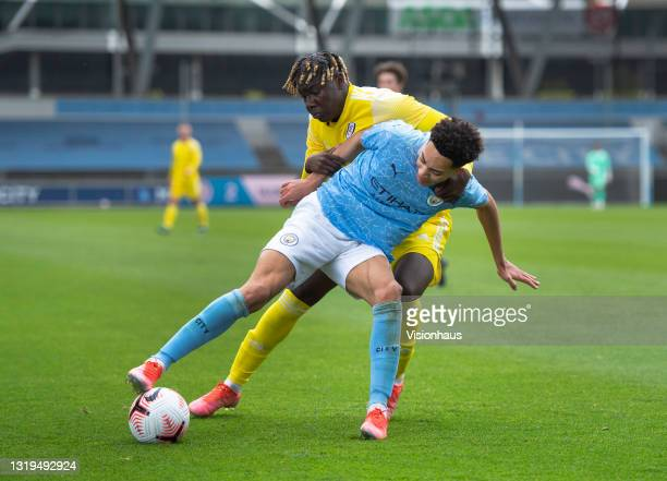 Sam Edozie of Manchester City and Idris Odutayo of Fulham in action during the U18 Premier League match between Manchester City and Fulham at The...