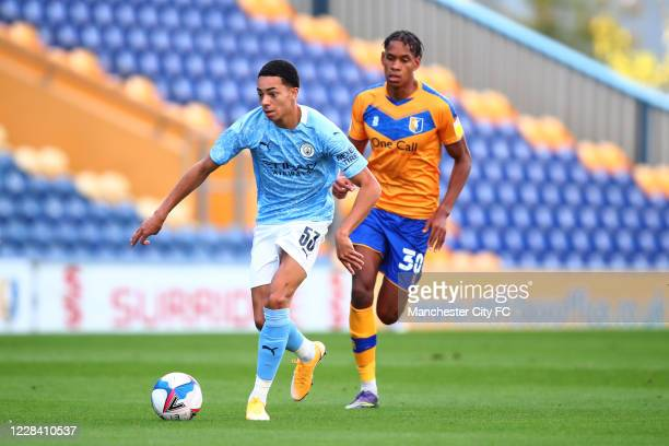 Sam Edozie of Manchester City in action with Alistair Smith of Mansfield Town during the EFL Trophy match between Mansfield Town and Manchester City...