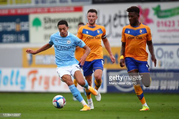Sam Edozie of Manchester City in action with Ollie Clarke and Rollin Menayese of Mansfield Town during the EFL Trophy match between Mansfield Town...