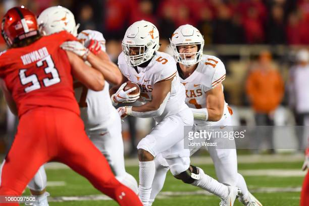 Sam Ehlinger hands off to Tre Watson of the Texas Longhorns during the first half of the game on November 10 2018 at Jones ATT Stadium in Lubbock...
