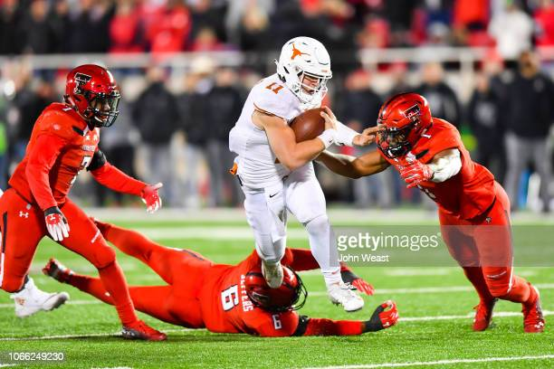 Sam Ehlinger of the Texas Longhorns gets past Riko Jeffers and Jordyn Brooks of the Texas Tech Red Raiders during the game against the on November 10...