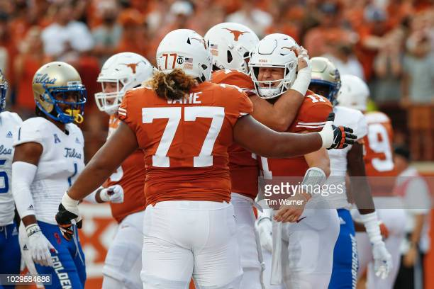 Sam Ehlinger of the Texas Longhorns is congratulated by Patrick Vahe and Elijah Rodriguez after a touchdown in the first quarter against the Tulsa...