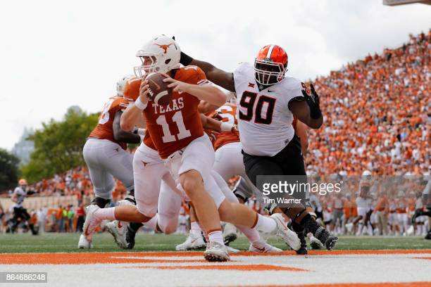 Sam Ehlinger of the Texas Longhorns is forced to scramble under pressure by Taaj Bakari of the Oklahoma State Cowboys in the second quarter at...