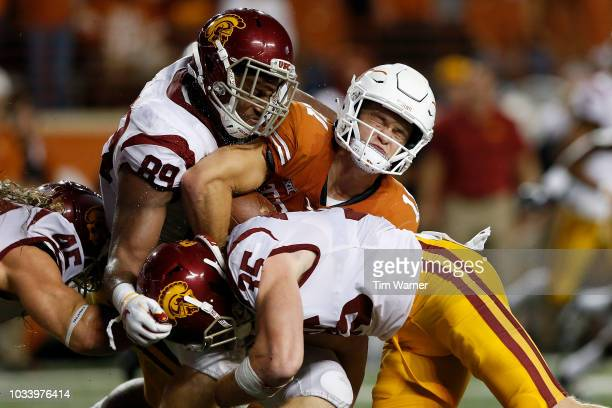 Sam Ehlinger of the Texas Longhorns is tackled by Christian Rector of the USC Trojans Cameron Smith and Porter Gustin in the second quarter at...