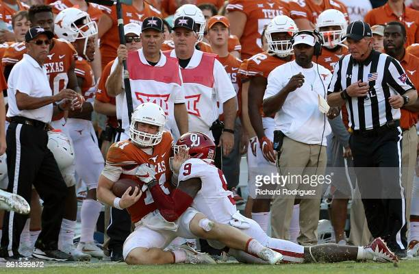 Sam Ehlinger of the Texas Longhorns is tackled by Kenneth Murray of the Oklahoma Sooners near the Texas sideline in the fourth quarter at Cotton Bowl...