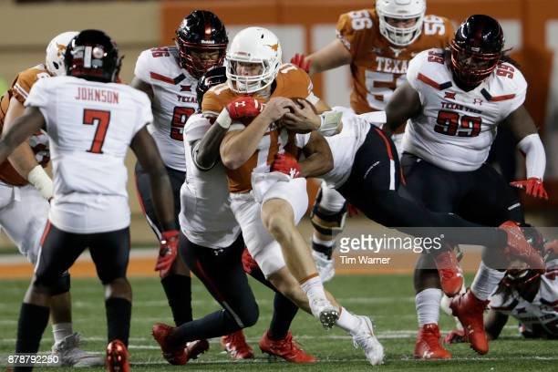 Sam Ehlinger of the Texas Longhorns is tackled by Kolin Hill of the Texas Tech Red Raiders and Jordyn Brooks in the fourth quarter at Darrell K...