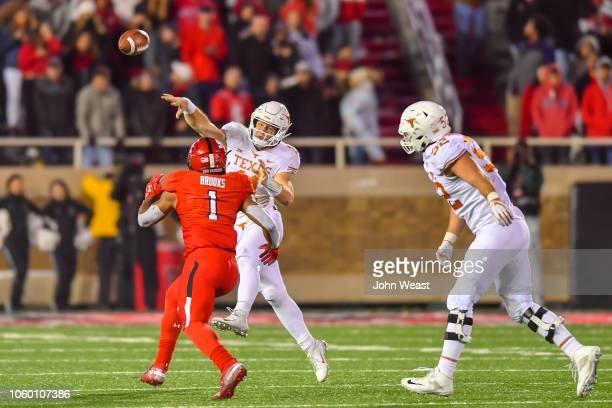 Sam Ehlinger of the Texas Longhorns passes the ball while under pressure from Jordyn Brooks of the Texas Tech Red Raiders during the 2nd half of the...