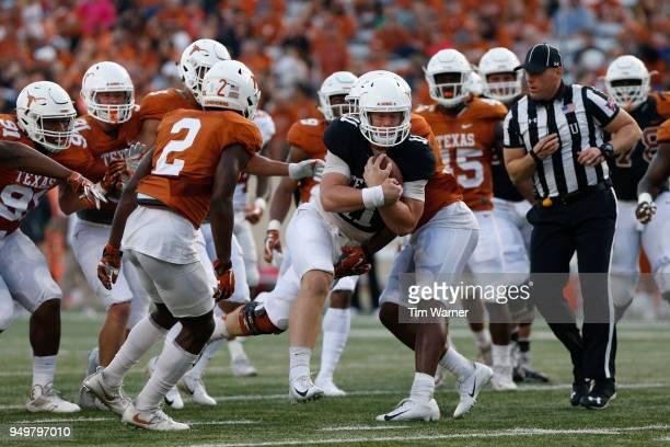 Sam Ehlinger of the Texas Longhorns runs through defenders in the first half during the OrangeWhite Spring Game at Darrell K RoyalTexas Memorial...
