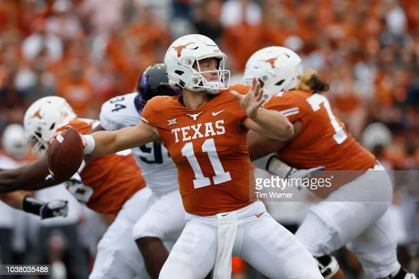 Sam Ehlinger of the Texas Longhorns throws a pass under pressure by Corey Bethley of the TCU Horned Frogs in the second quarter at Darrell K...