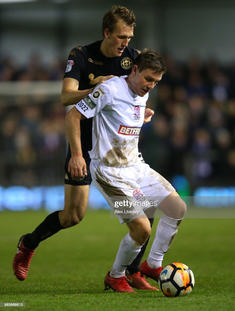 Sam Finley of AFC Fylde holds off a challenge from Dan Burn of Wigan Athletic during The Emirates FA Cup Second Round between AFC Fylde and Wigan Athletic on December 1, 2017 in Kirkham, England.