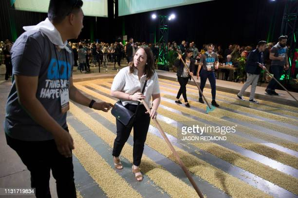 Sam Flaim a Starbucks store manager from Boise Idaho learns about the coffee raking with help from Starbucks barista JJ Montellano at the Annual...