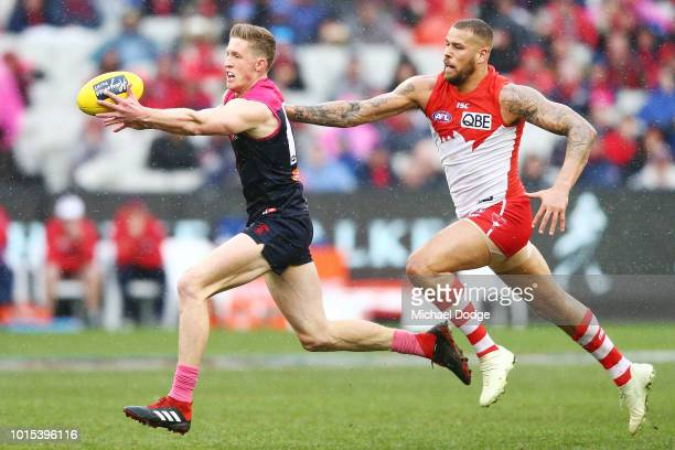 Sam Frost of the Demons gathers the ball and runs away from Lance Franklin of the Swans during the round 21 AFL match between the Melbourne Demons...