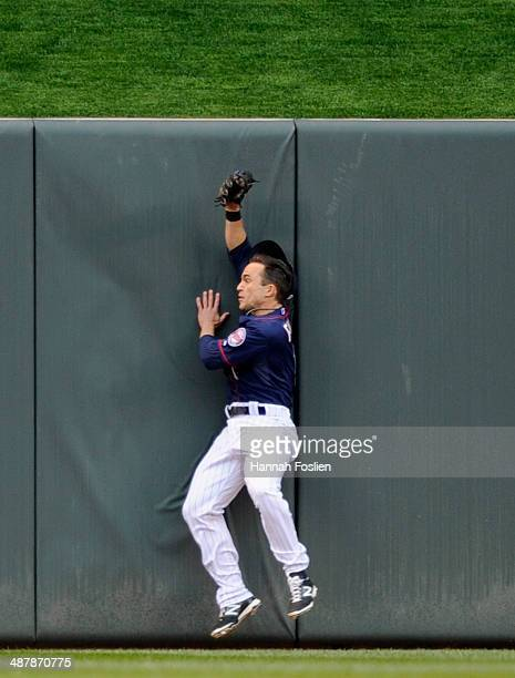 Sam Fuld of the Minnesota Twins hits the wall in center field after catching the ball hit by Manny Machado of the Baltimore Orioles during the first...
