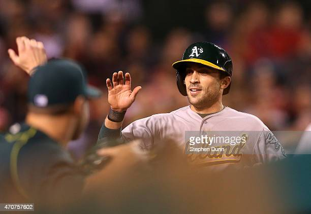 Sam Fuld of the Oakland Athletics celebrates as he returns to the dugout after scoring on a wild pitch in the seventh inning against the Los Angeles...