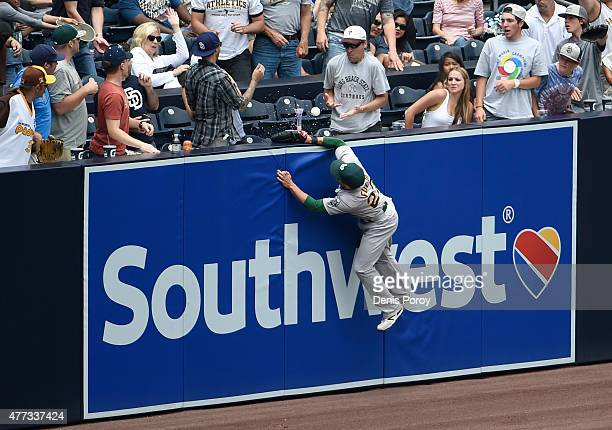Sam Fuld of the Oakland Athletics climbs the wall but can't make the catch on a home run hit by Austin Hedges of the San Diego Padres during the...