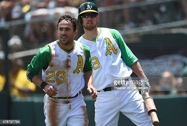 Sam Fuld of the Oakland Athletics is congratulated by Ben Zobrist after Fuld scored against the Kansas City Royals in the bottom of the first inning...