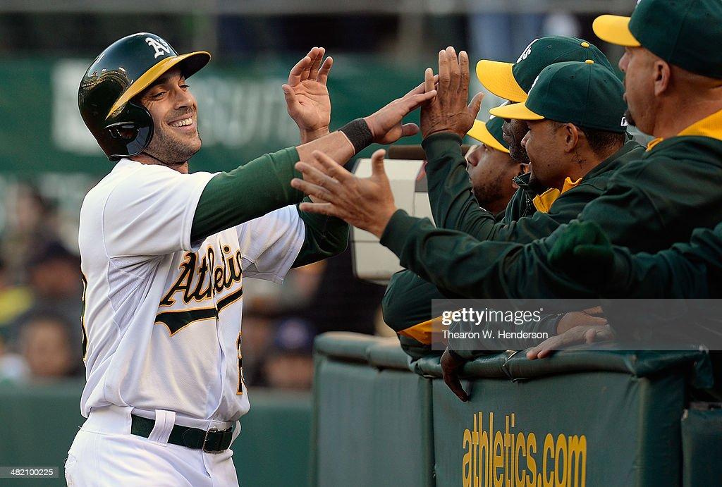 Sam Fuld #29 of the Oakland Athletics is congratulated by teammates after he scored against the Cleveland Indians in the bottom of the first inning at O.co Coliseum on April 2, 2014 in Oakland, California. Fuld scored on an RBI single from Jed Lowrie.