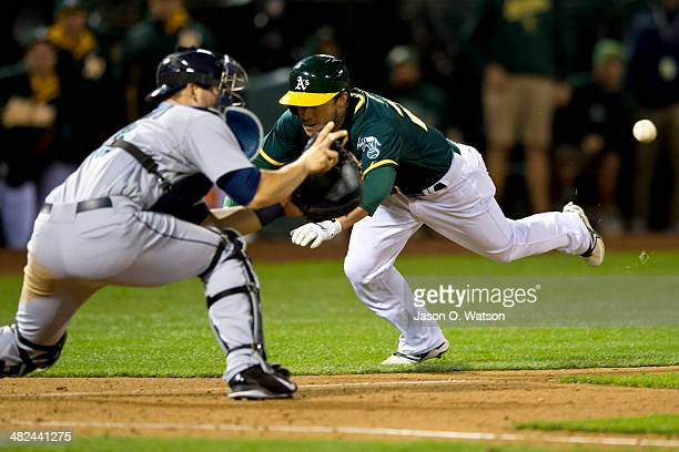 Sam Fuld of the Oakland Athletics is tagged out at home plate by Mike Zunino of the Seattle Mariners attempting to extend a triple into an in the...