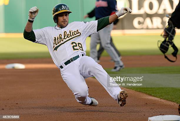 Sam Fuld of the Oakland Athletics slides into third base with a leadoff triple against the Cleveland Indians in the bottom of the first inning at Oco...