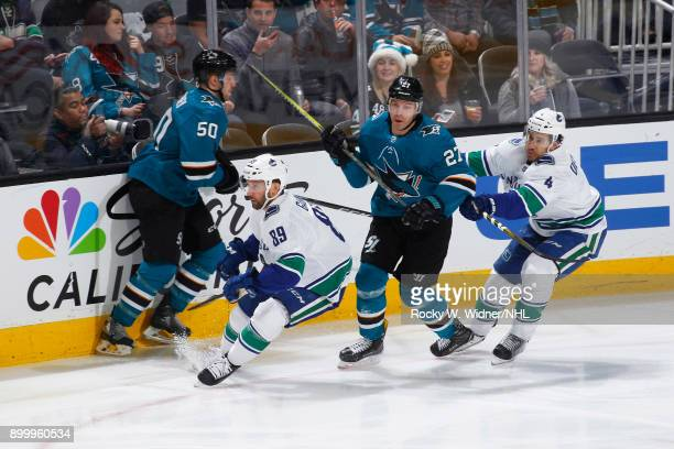 Sam Gagner and Michael Del Zotto of the Vancouver Canucks skate against Chris Tierney and Joonas Donskoi of the San Jose Sharks at SAP Center on...