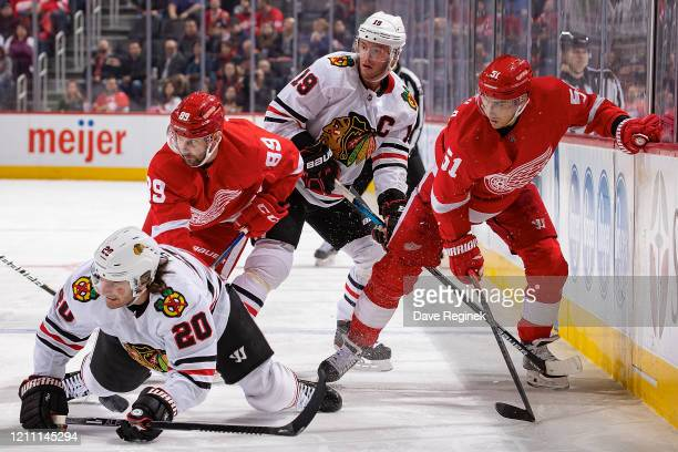 Sam Gagner and Valtteri Filppula of the Detroit Red Wings battles along the boards with Jonathan Toews and Brandon Saad of the Chicago Blackhawks...