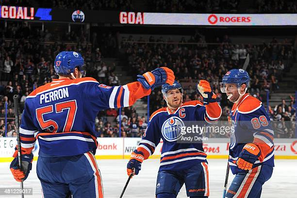 Sam Gagner, Andrew Ference and David Perron of the Edmonton Oilers celebrate after a goal in a game against the Anaheim Ducks on March 28, 2014 at...