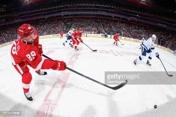 Sam Gagner of the Detroit Red Wings shoots the puck along the boards past Luke Schenn of the Tampa Bay Lightning during an NHL game at Little Caesars...
