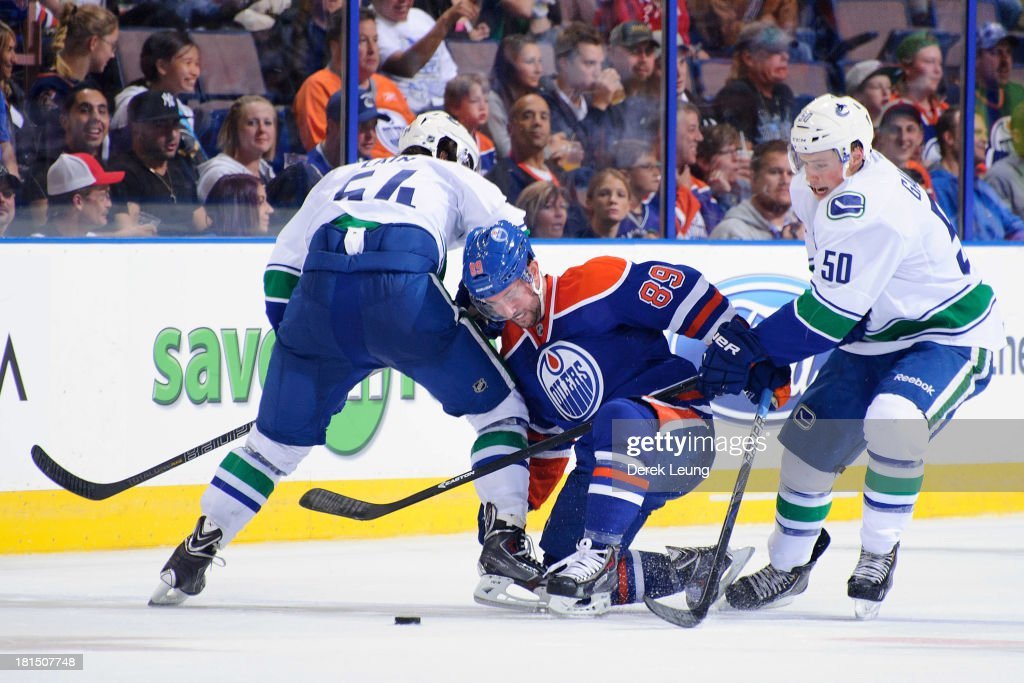 Sam Gagner #89 of the Edmonton Oilers gets checked by Kellan Lain #54 and Brendan Gaunce #50 of the Vancouver Canucks during a preseason NHL game at Rexall Place on September 21, 2013 in Edmonton, Alberta, Canada.