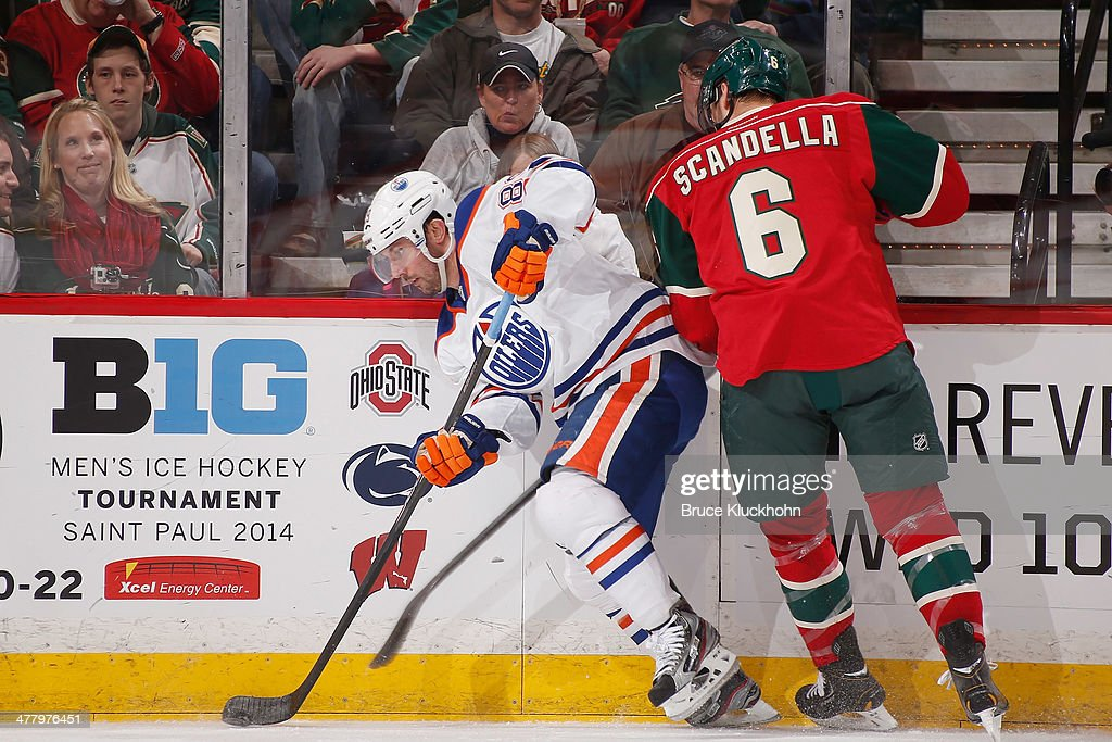 Sam Gagner #89 of the Edmonton Oilers handles the puck along the boards with Marco Scandella #6 of the Minnesota Wild defending during the game on March 11, 2014 at the Xcel Energy Center in St. Paul, Minnesota.