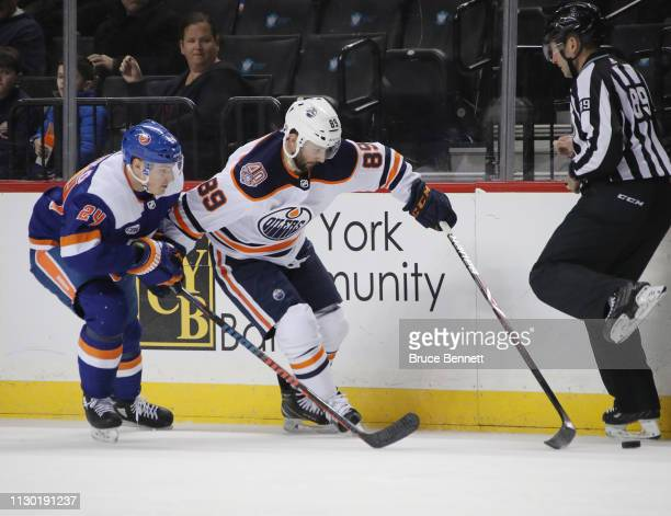 Sam Gagner of the Edmonton Oilers is held up by Scott Mayfield of the New York Islanders during the first period at the Barclays Center on February...