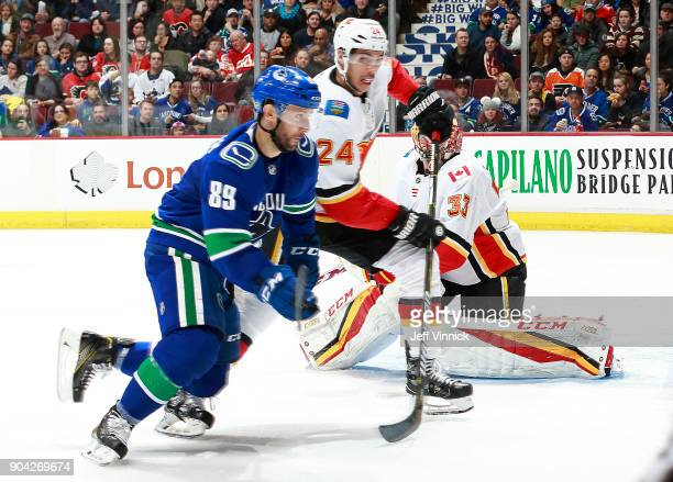 Sam Gagner of the Vancouver Canucks and Travis Hamonic of the Calgary Flames skate after the puck during their NHL game at Rogers Arena December 17...