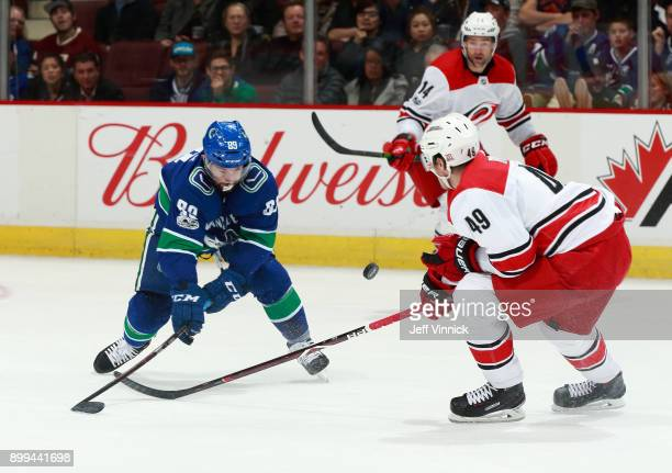 Sam Gagner of the Vancouver Canucks and Victor Rask of the Carolina Hurricanes watch a loose puck during their NHL game at Rogers Arena December 5...