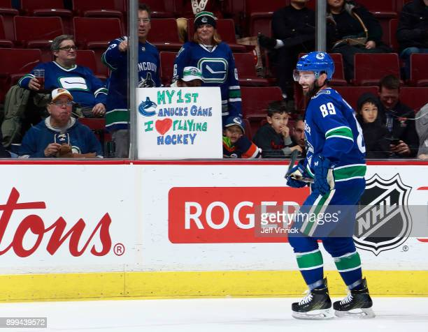 Sam Gagner of the Vancouver Canucks skates by a young fan during their NHL game against the Carolina Hurricanes at Rogers Arena December 5 2017 in...